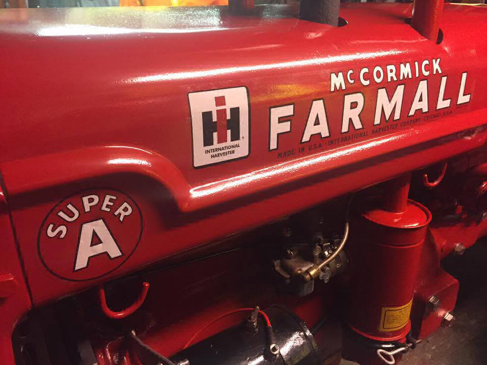 Close up of restored farm equipment with red powder coated parts and McCormik Farmall branding on side.