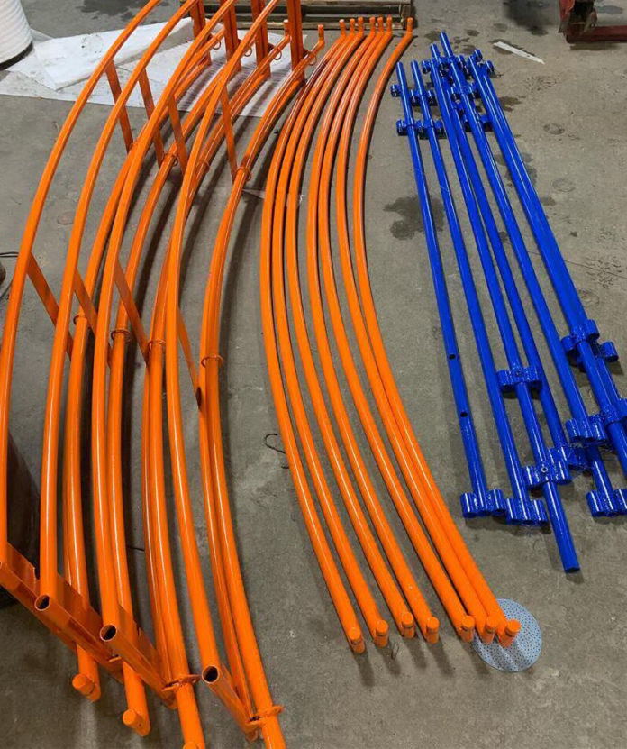Multiple long steel bars lay on ground powder coated blue and orange.