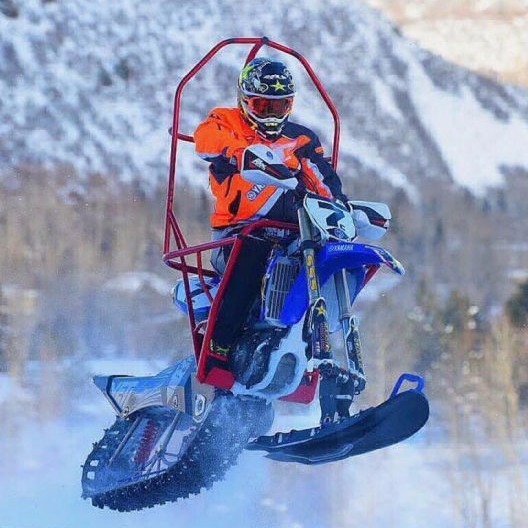 Recreational snow machine with powder coated parts, action shot in air with snow background.