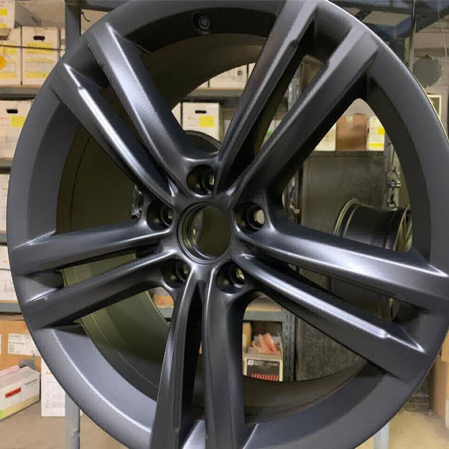 Newly powder coated tire rim with black matte finish.